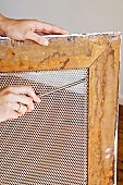 A wire mesh being fitted into a picture frame