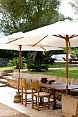 White parasols shading seating on terrace in Mediterranean garden