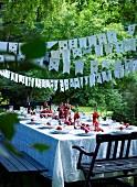 Festive set table below bunting strung between trees in garden