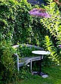 Alte Gartenbank und Bistrotisch vor Hecke