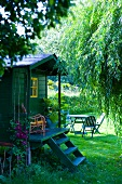 Garden shed with front steps to porch and seating area on lawn