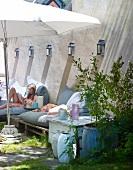 Children relaxing on cushioned garden furniture below parasol