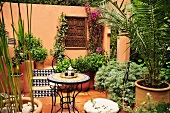 Üppig bepflanzte Terrasse mit rundem Gartentisch (Marokko)