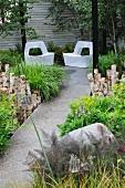 Üppig begrünter Gartenweg und Sitzecke mit zwei Gartenstühlen