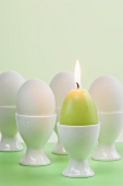 Easter eggs and egg-shaped candle in egg cups