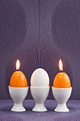 Easter egg and egg-shaped candles in egg cups