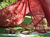 Wooden deckchair beneath fluttering canopy