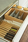 Organised cutlery draw with wooden compartments and knife block