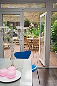 View of planted patio with decking through open terrace door from kitchen-dining room