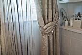Elegant brocade curtain and striped translucent curtain at bathroom window