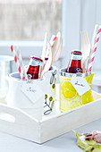 Home-made place setting tins holding cutlery, small drinks bottles and straws