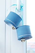 Decorative blue bells made of small tin cans hanging from a door handle