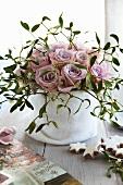 Strauss aus rosafarbenen Rosen und Misteln