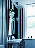 Washstand against black and white striped wall paper in vintage bathroom