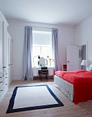 Red bedspread on bed in white bedroom