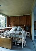 Vintage bed with white-painted metal frame in rustic bedroom