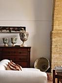 weiße Recamiere vor antiker Kommode mit pokalartigen Vasen in mediterranem Wohnraum