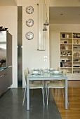 Set dining table in open-plan kitchen in front of several clocks on narrow wall panel