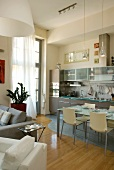 Open-plan interior with modern dining table and chairs in front of fitted kitchen