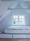 Attic room with mattress and bedding on white platform with drawers in front of window