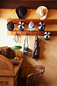 Hats and caps hanging on pegs above wooden, vintage-style desk and chair