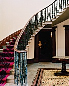 Curved staircase with modern runner in traditional foyer