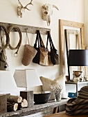 Rustic shelf and rack in corner with leather bags hanging from pegs