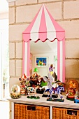 Toys on cabinet in front of mirror with whimsical frame leant on a stone wall