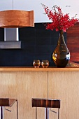 Red flowering twigs in vase on kitchen counter and partial view of designer bar stools