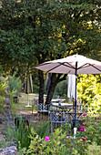 Quiet corner of rose garden with parasol and metal garden furniture beneath shady trees