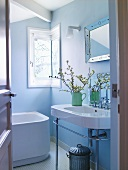 View through open door of washstand in bathroom painted light blue