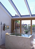 Cubist bathtub full of water below sloping glass roof and with view through terrace window