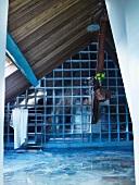 Dachraum mit Trennwand aus Glasbausteinen und holzverkleidete Schräge