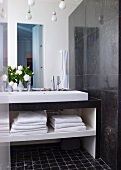 Modern washstand with towels in open-fronted shelves below next to dark marble wall