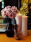 Flowers, candles and pistachios on a table