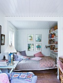 Comfortable bedroom with white wood panelling on walls and ceiling