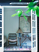 View through terrace door of wicker armchair and rustic table