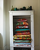 Stack of colourful blankets and cushions in open-fronted cupboard