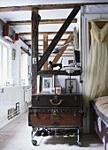 Stack of vintage suitcases on trolley in open-plan interior with old half-timbered structure