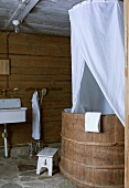 White fabric canopy over rustic tub in bathroom