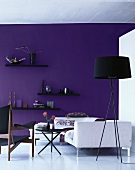 Showroom - black standard lamp and white sofa in front of purple-painted wall