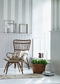 Basket chair in corner of bright room in front of white, half-height wood panelling
