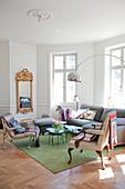 Wohnzimmerecke mit Sitzmöbeln und Bogenlampe in einer Altbauwohnung