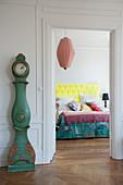 Vintage Standuhr neben offener Schlafzimmertür und Blick auf Doppelbett mit gelbem Kopfteil