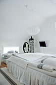 Pale, Scandinavian-style attic bedroom with spherical pendant lamp above bed