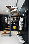 Cloakroom foyer with black-painted wooden walls and spiral staircase: black and white portraits and bright yellow classic chair in background