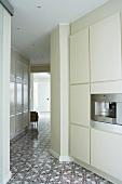 Open-plan, designer kitchen with ornamental, patterned tiled floor