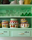 Detail of kitchen shelves holding glasses and bowls in a mixture of Art Deco and 70s styles
