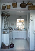 Baskets hanging above open doorway leading to country house kitchen