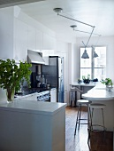 Open-plan kitchen with anglepoise ceiling lamps above white counter running along the wall